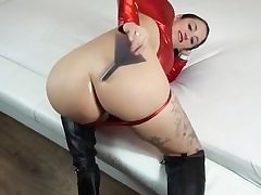 Jiggly looking dark haired in her red costume poses on camera like a real whore